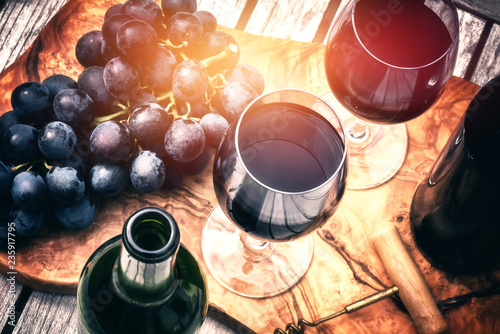 Photo Setting with bottles of red wine and glasses
