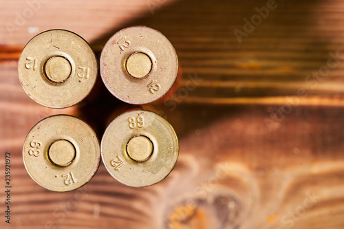 Hunting shells and 12 gauge cartridges on wooden background