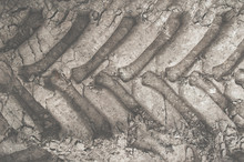 Imprint Of The Jeep Tire On The Gray Earth. Tractor Wheel On The Ground. Tire Protector Close-up. Gray Sand Background. SUV.