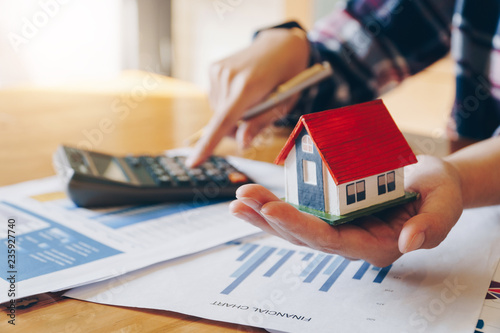 Pinturas sobre lienzo  Woman holding house model in hand and calculating financial chart for investment to buying property