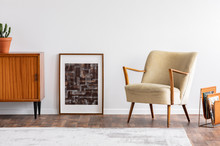 Abstract Graphic In Wooden Frame Between Retro Cabinet With Plant And Elegant Beige Armchair, Real Photo
