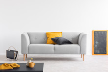 Yellow And Black Pillows On Grey Settee In Spacious Living Room Interior With Blackboard In Orange Frame And Magazine Rack On The Floor