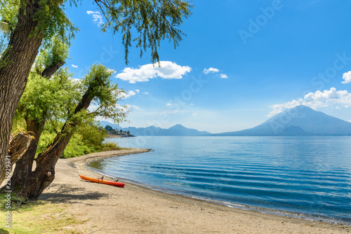 Tuinposter Centraal-Amerika Landen Paradise beach with chair and kayak at lake Atitlan, Panajachel - Relaxing and recreation at beach with vulcano landscape scenery in the highlands of Guatemala