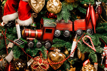 Background Of Fir Tree With Red Toy Train And Christmas Decoration