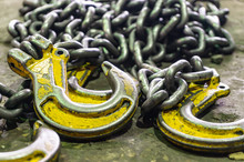 Chains Made Of Iron With Hooks Of Yellow Color, For Raising A Large Load, Lie On The Floor In The Production Workshop. Abstract Industrial Background.