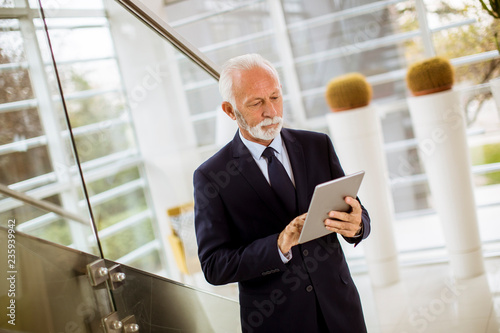 Senior businessman using digital tablet in the office