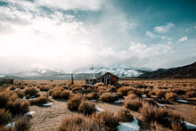 Small House In A Field With Snow Covered Mountains In The Distance