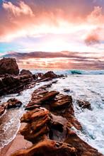 Waves Crashing Against Rocks At Sunset