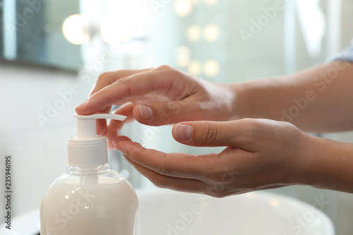 Fotografie, Obraz  Woman applying liquid soap on hand in bathroom, closeup
