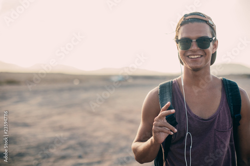 Portrait Of Young Handsome cheerful guy in sunglasses on the roadside.