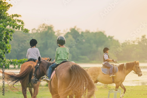 Fotografia Kids learn to ride a horse near the river before sunset.