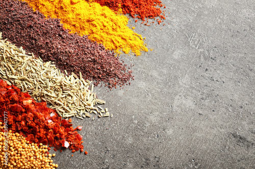 Rows of different aromatic spices and space for text on gray background