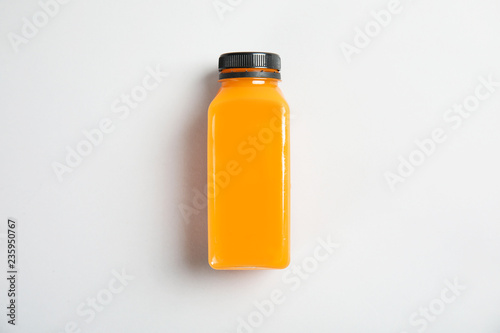 One bottle with tasty drink on color background, top view