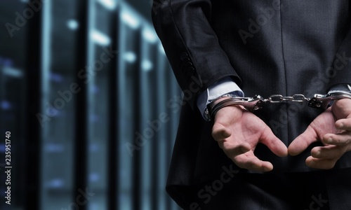 Fototapeta  Cropped image of male hands in handcuffs behind his back