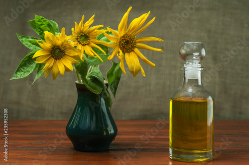 Fotobehang Kruiderij Sunflower oil in a glass decanter and a sunflowers in a vase on a background of burlap.