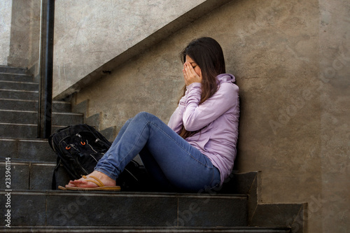depressed student woman or bullied teenager girl sitting outdoors on street stai Canvas Print