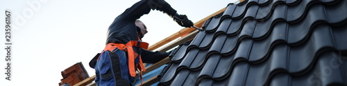 Fotografia Dachdecker bei der Arbeit mit schwarzen Dachsteinen, web slider