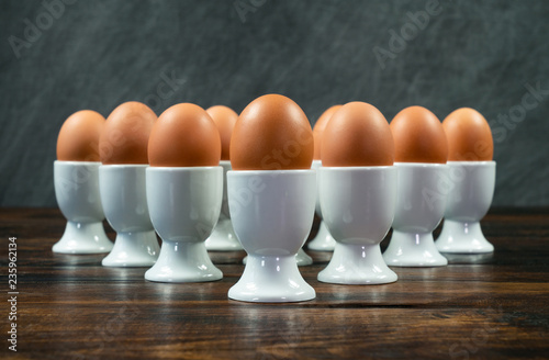 Ten Boiled Eggs in Egg Cups on a Table