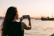 Young woman taking photo of ship on water at sunset