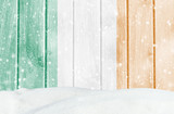 Christmas winter background with wooden wall, falling snow, snowdrift and Irish flag
