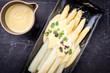 Traditionell gekochter weißer Spargel  mit Sauce Hollandaise und Kräuter als Draufsicht auf einem Teller
