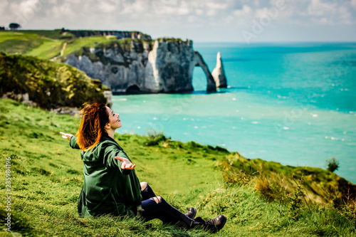 Obraz na płótnie photo of beautiful young woman relaxing and looking at the splendid Etretat