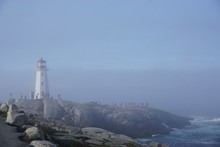 Peggy's Cove, Nova Scotia, Canada: Peggy's Point Lighthouse (1914) Shrouded In Morning Mist With Waves Breaking On A Rocky Coast.