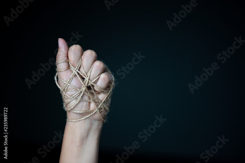 Valokuva  a woman hand tied with wire on dark background in low key