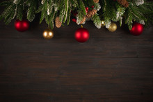 Christmas Background With Fir Tree Green Branches, Greeting Card With Decoration In Red And Golden Colors On Dark Brown Wooden Board, Copy Space Banner