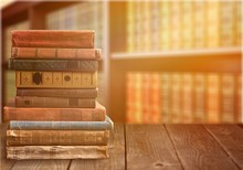 Collection Of Old Books On Wooden Table On Room Background