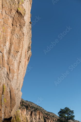 Fotografie, Obraz  Vertical view of overhanging sandstone cliff with colorful lichen in Bandelier N