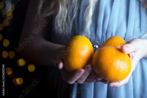 girl holding tangerines