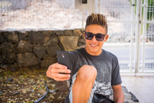 Young Handsome Teenager Boy 15 Years Old Take Selfie Picture With Mobile Phone Smiling To The Device - Social Media Life For Influencer And Blogger - New Work With Internet