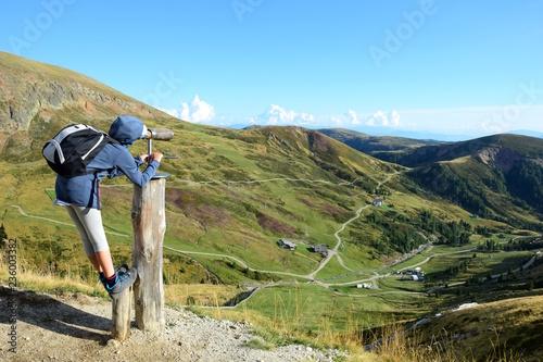 Fotografia, Obraz  Junges Mädchen betrachtet durch ein Fernrohr die wunderschöne Landschaft in Südt