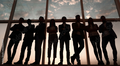 Fotografía  silhouette of a group of business people standing near the office window