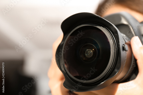 Female photographer with professional camera on blurred background, closeup Canvas Print