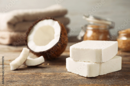 Handmade soap bars and coconut on wooden table. Space for text