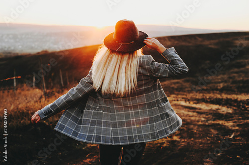 Pinturas sobre lienzo  Back view of young female in trendy hat and jacket standing in amazing countryside during magnificent sundown