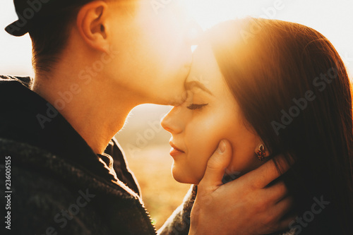 Side view of crop male kissing pretty girlfriend in forehead while spending time in nature on sunny day Canvas-taulu