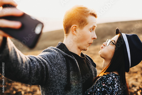 Side view of young man and woman making funny faces and looking at each other while taking selfie on background of beautiful nature Wallpaper Mural