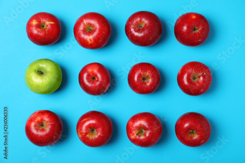 Fotomural  Green apple among red ones on color background, top view