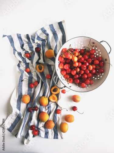 Overhead view of cherries and apricots in strainer and napkin