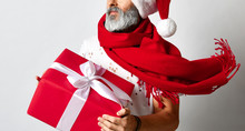 Senior Bearded Man Holding Red Gift Box Over Grey Background Looking At The Corner