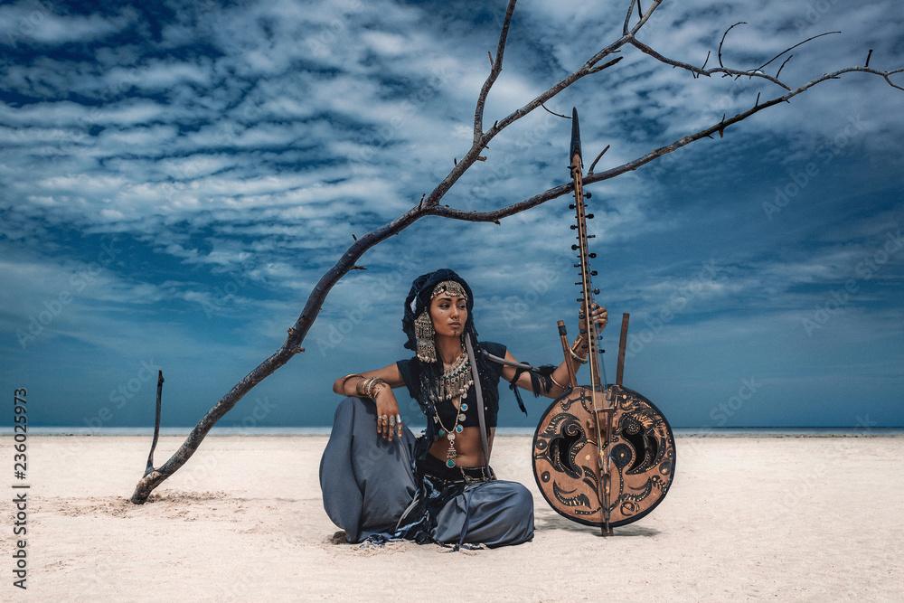 Fototapeta Beautiful young stylish tribal dancer. Woman in oriental costume outdoors