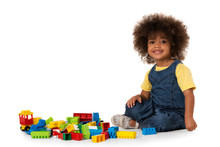 Cute Little African American Girl Playing With Lots Of Colorful Plastic Blocks Indoor. Isolated