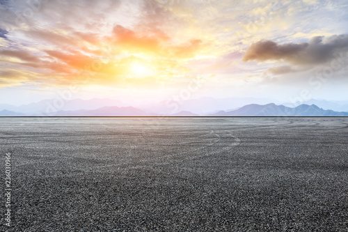 Poster Gris Asphalt road pavement and mountain at beautiful sunset