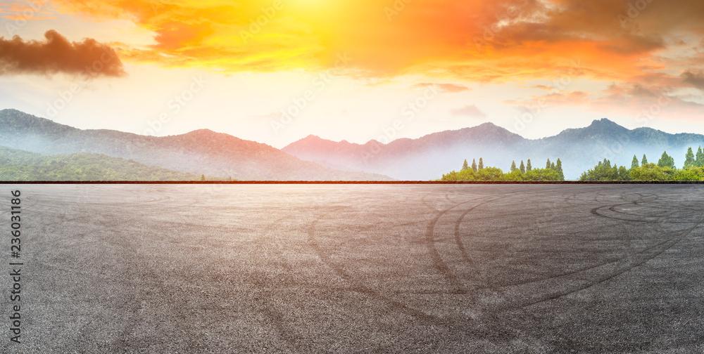 Fototapeta Asphalt road pavement and mountain at beautiful sunset