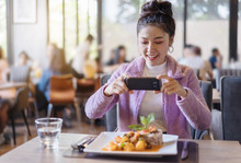 Woman Using Smartphone Take Photo Of Food Before Eating In Restaurant