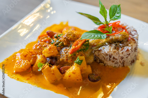 duck confit with red curry served with brown rice on plate