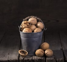 Walnuts  In A Basket On Wooden Table